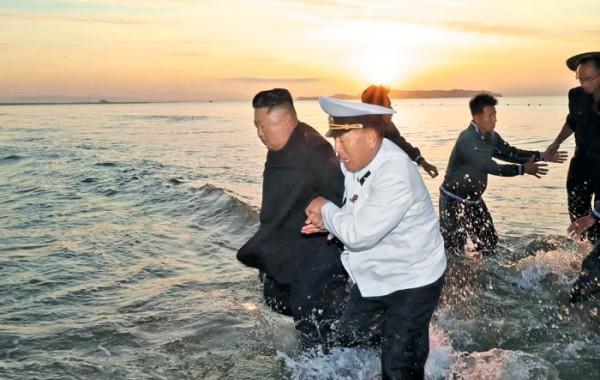 김정은 북한 국무위원장이 지난 24일 인민복 차림으로 바다에 들어가 참모들과 함께